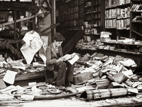 Young boy reading book in a ruined bookshop in London devastated by an air raid - 1940